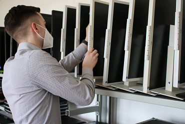 Employee examines a collection of monitors